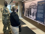 A man in a military uniform speaks to a woman in uniform while standing in front of an historical mural with summary text about the history of DLA Troop Support in Philadelphia.