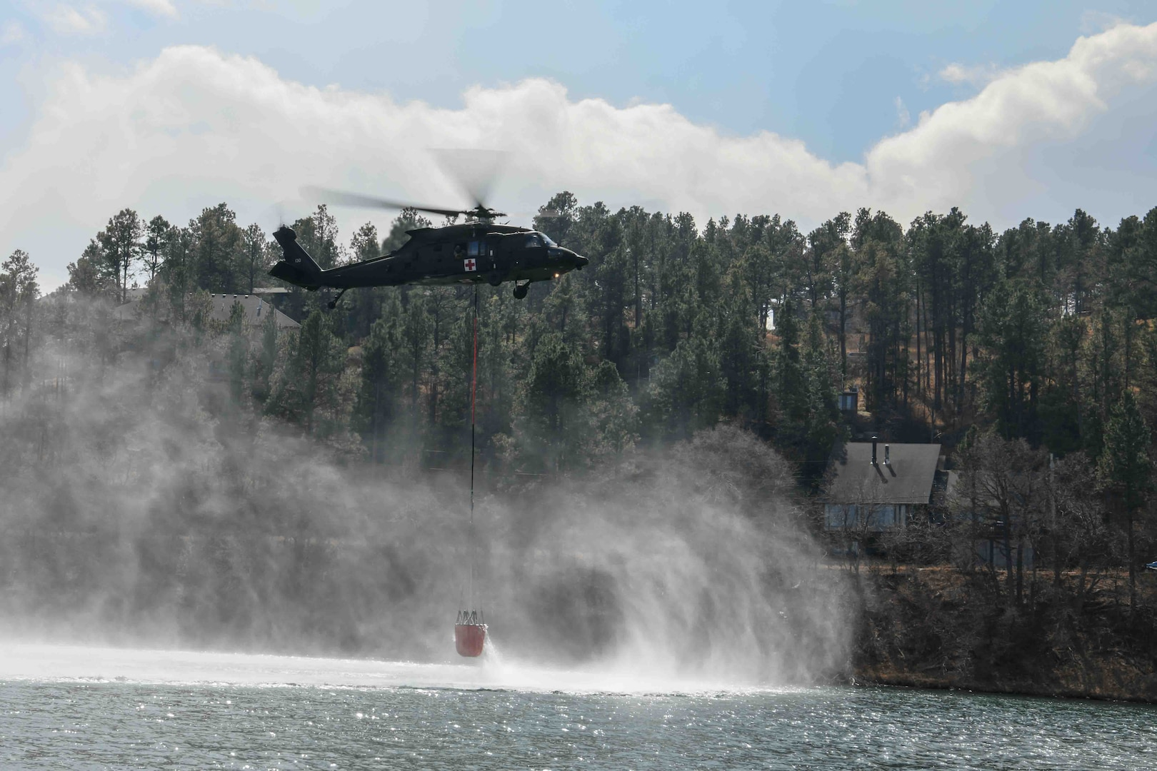 A South Dakota National Guard HH-60 Black Hawk helicopter dips a water bucket into Canyon Lake to help fight Schroeder's Fire in Rapid City, S.D., March 30, 2021. Several dozen South Dakota National Guard members supported local, state and federal agencies to help extinguish the fire.