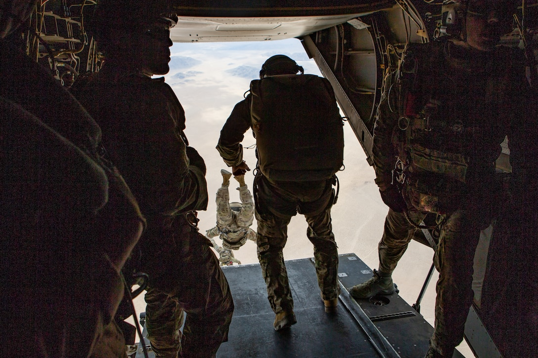 U.S. Army Soldiers assigned to 10th Special Forces Group (Airborne) free fall out of an MV-22B Osprey helicopter with Marine Medium Tiltrotor Squadron (VMM) 365 at Marine Air-Ground Combat Center, California, April 1, 2021. Marines with Marine Medium Tiltrotor Squadron 365 and Soldiers with 10th SFG (A) prepare for future conflicts in the integrated and joint environment provided by Service Level Training Exercise (SLTE) 3-21. SLTE is a series of exercises designed to train Marines for operations around the globe by increasing their ability to operate and conduct offensive and defensive combat operations. VMM-365 is a subordinate unit of 2nd Marine Aircraft Wing, the aviation combat element of II Marine Expeditionary Force. (U.S. Marine Corps photo by Lance Cpl. Elias E. Pimentel III) (This photo has been altered for security purposes by blurring out the servicemember's face and other personal identifying elements.)