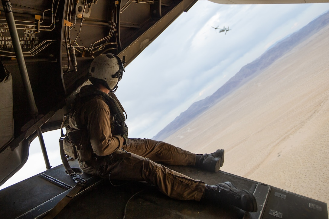 U.S. Marine Corps Cpl. Logan G. Snyder, a crew chief with Marine Medium Tiltrotor Squadron (VMM 365), observes an MV-22B Osprey helicopter during a reconnaissance parachute flight with U.S. Army Soldiers assigned to 10th Special Forces Group (Airborne) at Marine Air-Ground Combat Center, California, April 1, 2021. Marines with Marine Medium Tiltrotor Squadron 365 and Soldiers with 10th SFG (A) prepare for future conflicts in the integrated and joint environment provided by Service Level Training Exercise (SLTE) 3-21. SLTE is a series of exercises designed to train Marines for operations around the globe by increasing their ability to operate and conduct offensive and defensive combat operations. VMM-365 is a subordinate unit of 2nd Marine Aircraft Wing, the aviation combat element of II Marine Expeditionary Force. (U.S. Marine Corps photo by 2nd Lt. Hudson E. Sadler)