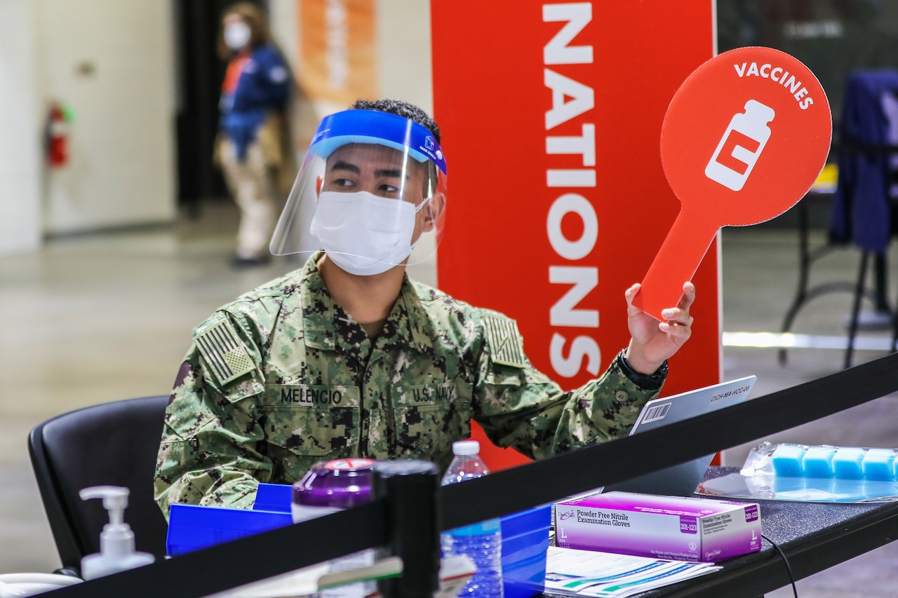 "A soldier wearing a face mask and shield sits at a table holding medical supplies and holds up a sign bearing the word ""vaccines."""