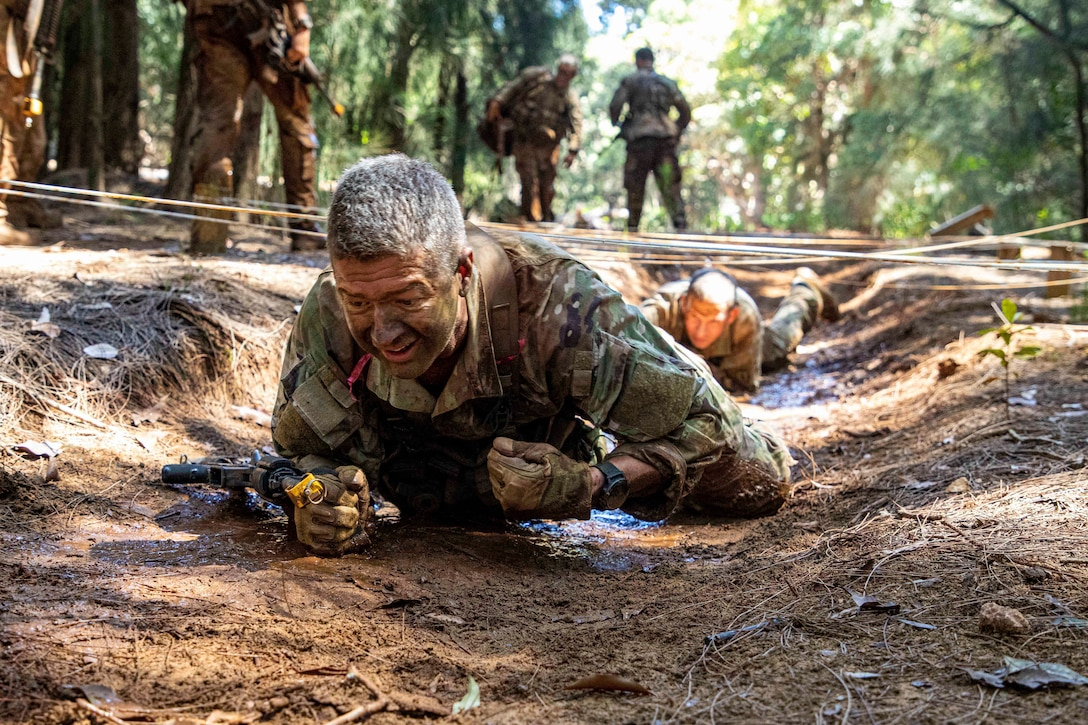 Soldiers crawl under an obstacle course  in the woods.