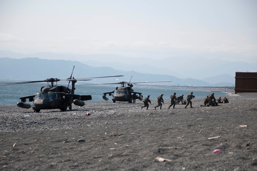 Marines carrying weapons run out of helicopters parked on the beach.