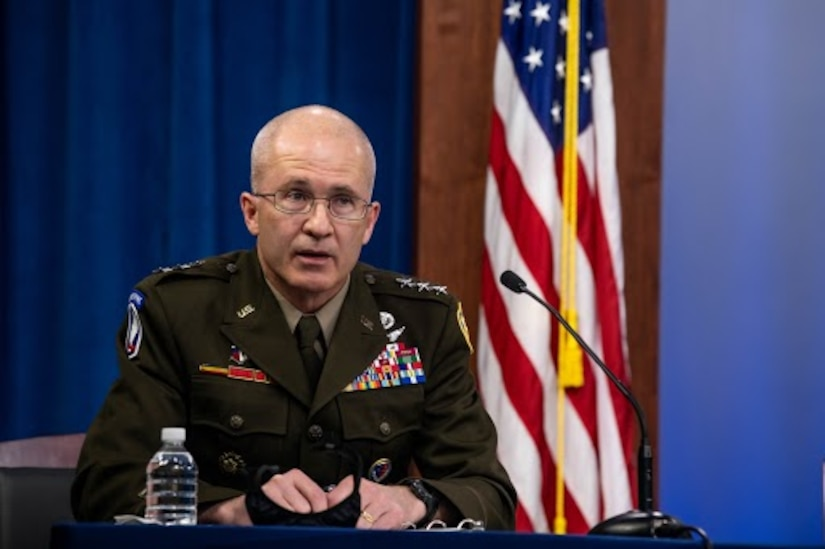 A man in an Army uniform speaks into a microphone.