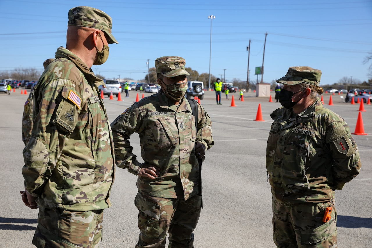 Three soldiers wearing face masks speak to each other.