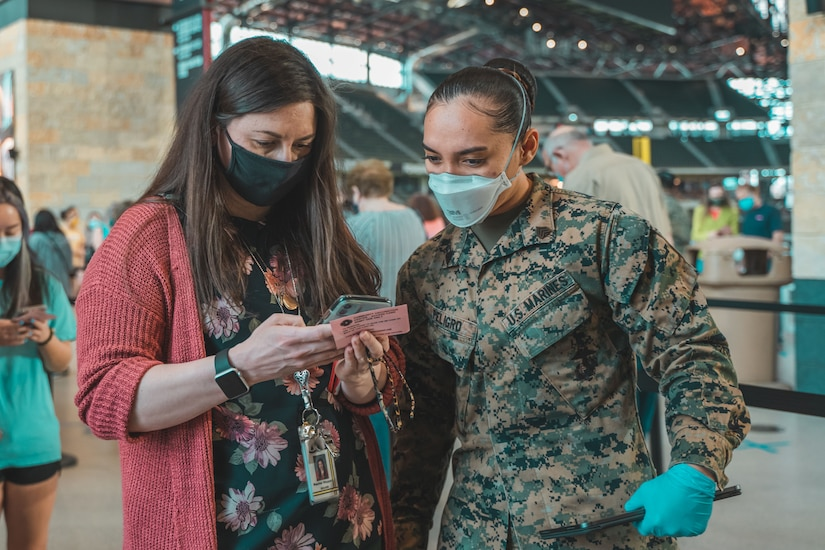 A soldier speaks with a woman who is looking at her phone.