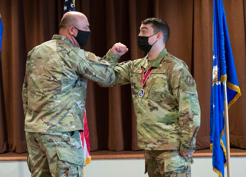 Col. Patrick Miller, 88th Air Base Wing commander, elbow-bumps Staff Sgt. Marc Lejeune during the Airman Leadership School Class 21-C graduation ceremony inside the base club at Wright-Patterson Air Force Base, Ohio, March 25, 2021. Miller recognized and presented a coin to Lejeune at the graduation for initiating basic first aid to a neighbor March 23.