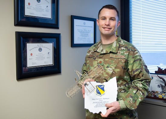 Maj. David Tubman stands in his office with the 88th Air Base Wing's 2020 Field Grade Officer of the Year Award for his work in the 88th Medical Group's Mental Health Clinic. U.S. Air Force photo/Wesley Farnsworth