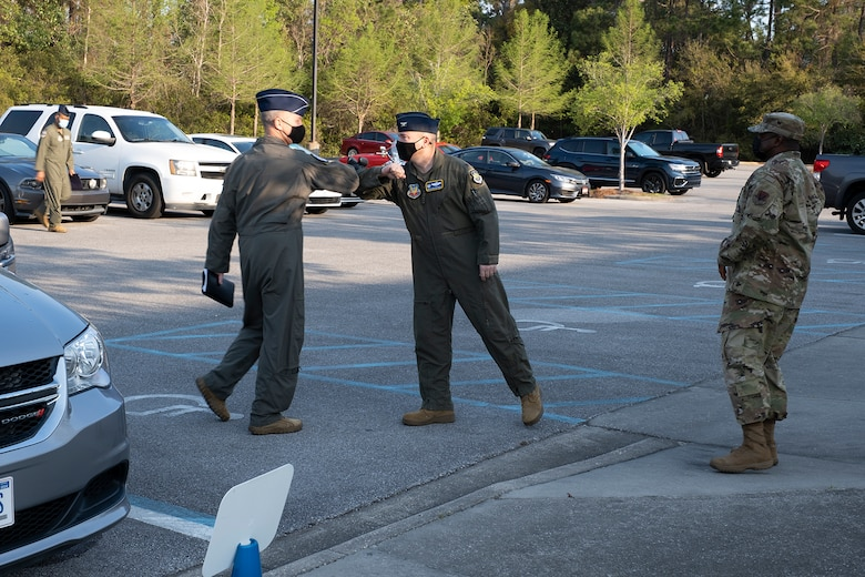 photo of two Airmen greeting the other