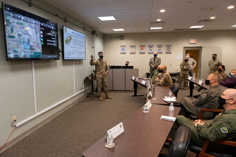 Photo of Airman briefing group of individual seated at tables