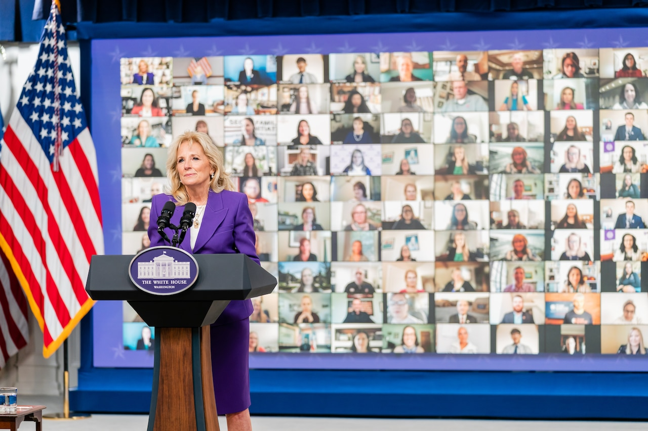 A woman in a suit stands behind a lectern with microphones. A sign on the lectern indicates that she is at The White House. A collage of monitors is behind her.