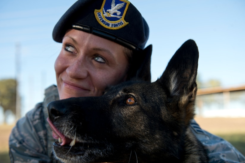 Senior Airman Chelsea LaFever, a military working dog handler from the 802nd Security Forces Squadron, smiles with her dog ZZusa after training at Joint Base San Antonio-Lackland. Upon completion of training tasks, LaFever encourages ZZusa with a treat. LaFever and ZZusa have been training and developing chemistry to complete the day-to-day mission at JBSA-Lackland. (U.S. Air force photo/Staff Sgt. Vernon Young Jr.)