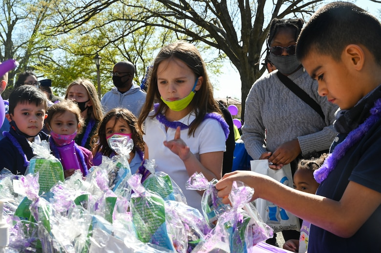 Military children grab gift bags during the Military Child Parade at Barksdale Air Force Base, Louisiana, April 1, 2021.