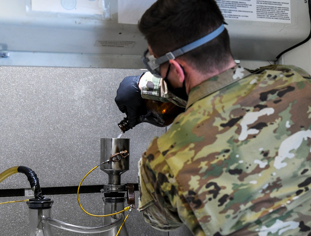 Staff Sgt. Brian Elrod, 436th Logistics Readiness Squadron fuels laboratory noncommissioned officer in charge, pours fuel into a bottle-method funnel during the fuel testing process at Dover Air Force Base, Delaware, Jan. 12, 2021. The bottle-method test measures levels of water, additives, sediment and particulates in fuel to ensure all aircraft receive the cleanest fuel possible. (U.S. Air Force photo by Airman 1st Class Stephani Barge)