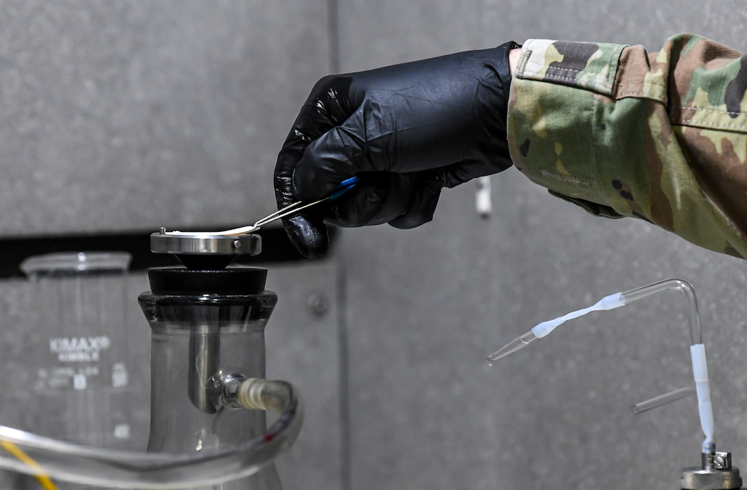 Staff Sgt. Brian Elrod, 436th Logistics Readiness Squadron fuels laboratory noncommissioned officer in charge, removes a micron filter during the bottle method testing process at Dover Air Force Base, Delaware, Jan. 12, 2021. The micron filter is weighed before the bottle test, and a gallon of fuel is then poured through the filter to collect particulates. The filter is then dried and weighed again. The weight difference determines how much particulate is in a given sample of fuel. (U.S. Air Force photo by Airman 1st Class Stephani Barge)