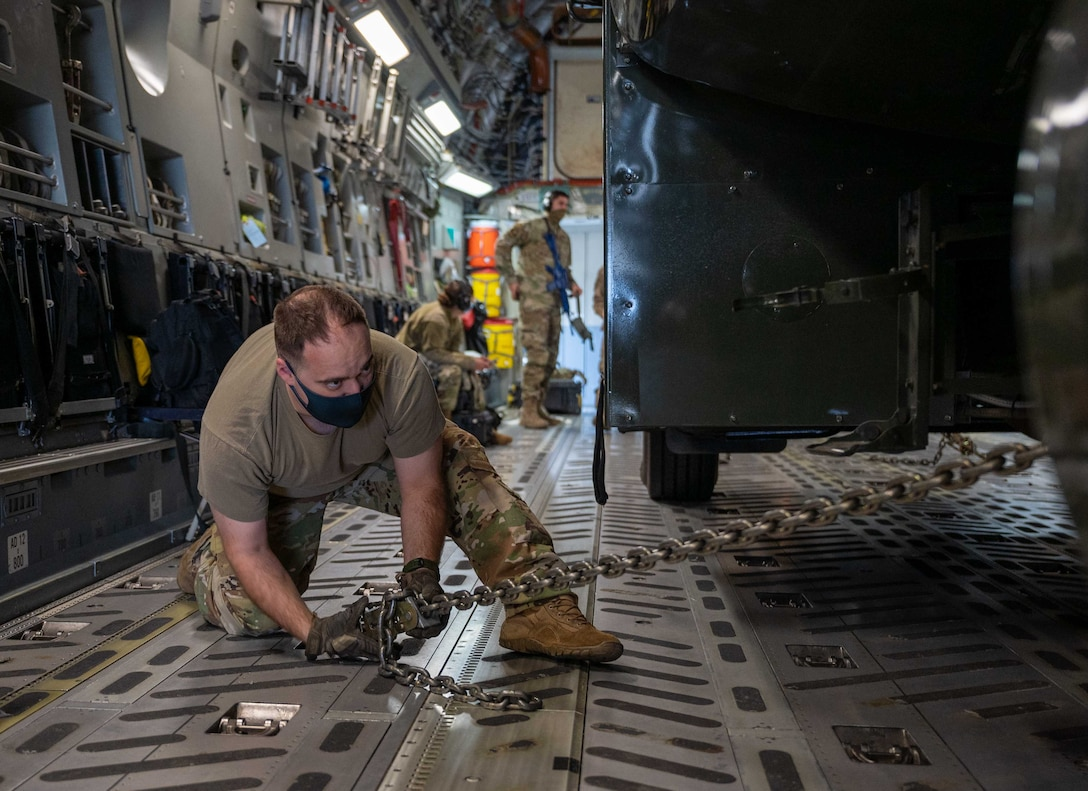 Senior Airman Eric Jones, 3rd Airlift Squadron loadmaster, chains a fuel truck to the cargo floor of a Dover Air Force Base C-17 Globemaster III during exercise Razor Talon at Seymour Johnson AFB, North Carolina, March 23, 2021. Team Dover's Multi-Capable Airmen program developed and equipped seven Airmen to perform tasks outside of their Air Force Specialty Codes. RT was the first time an MCA team from Dover AFB participated in an exercise. (U.S. Air Force photo by Airman 1st Class Faith Schaefer)