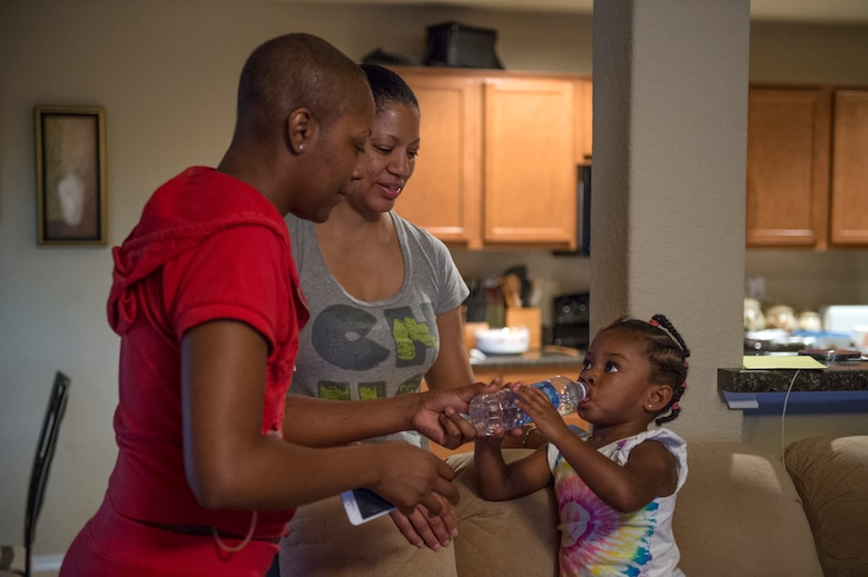 Somaya, 2, daughter of Staff Sgt. Chantel Thibeaux, Joint Base-Fort Sam Houston, Texas, dental assistant instructor, stands on the couch while her mother and grandmother Carla watch her drink water.  At two years old, Somaya is unaware of her mothers battle with cancer and tried to play with her every chance she can, but is limited to certain activities. About 15 family and friends gathered at her house to celebrate a successful surgery and provide love to Thibeaux during her quest to defeat cancer. (U.S. Air Force photo/Staff Sgt. Vernon Young Jr.)