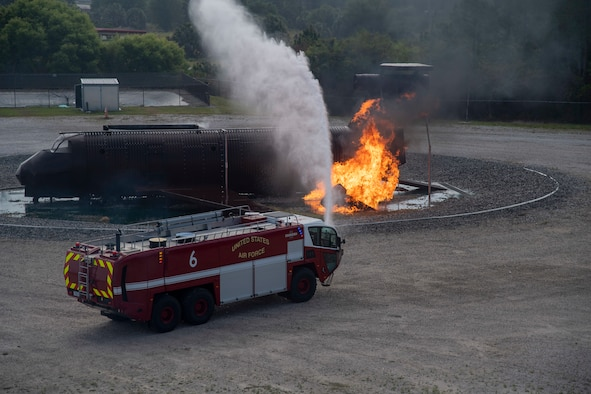 A firetruck assigned to the 6th Civil Engineer Squadron (CES) suppresses a fire during a live-burn exercise at MacDill Air Force Base, Fla, March 23, 2021.