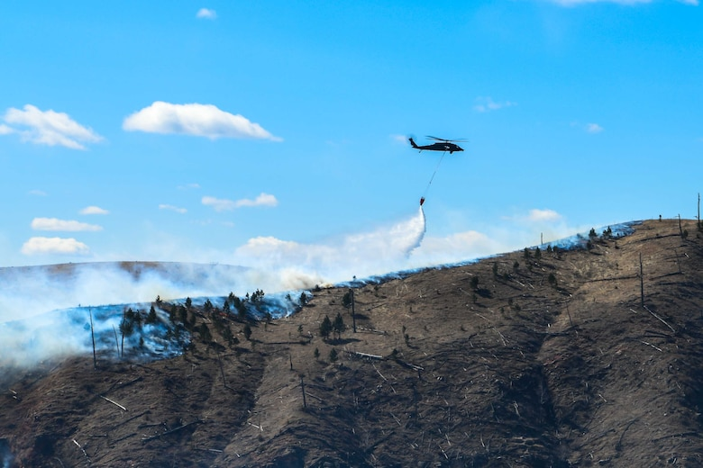 Hawk helicopter drops water from its bucket to help fight Schroeder's Fire in Rapid City, S.D., March 30, 2021. The fire started March 29 in the Black Hills four miles west of Rapid City.
