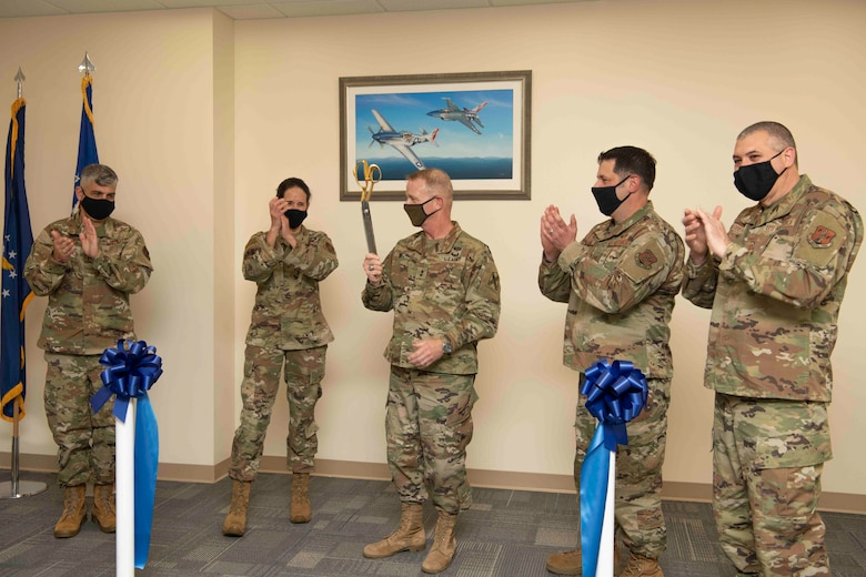 U.S. Air Force leaders applaud during a ribbon cutting ceremony