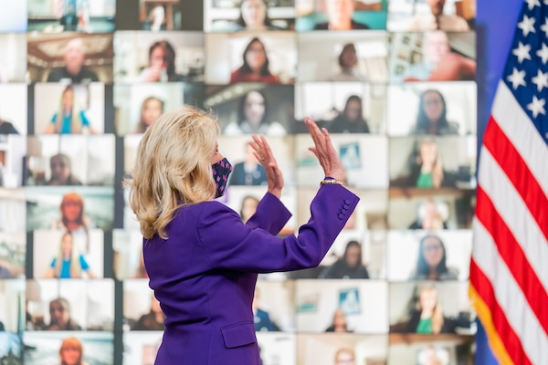 A woman in a suit, with her back to the camera, holds up both hands to the monitors that were behind her showing the faces of those virtually attending the event. An American flag is to her right.