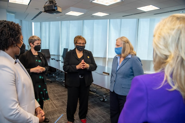 Five women stand in a semicircle visit with each other at  a military call center.