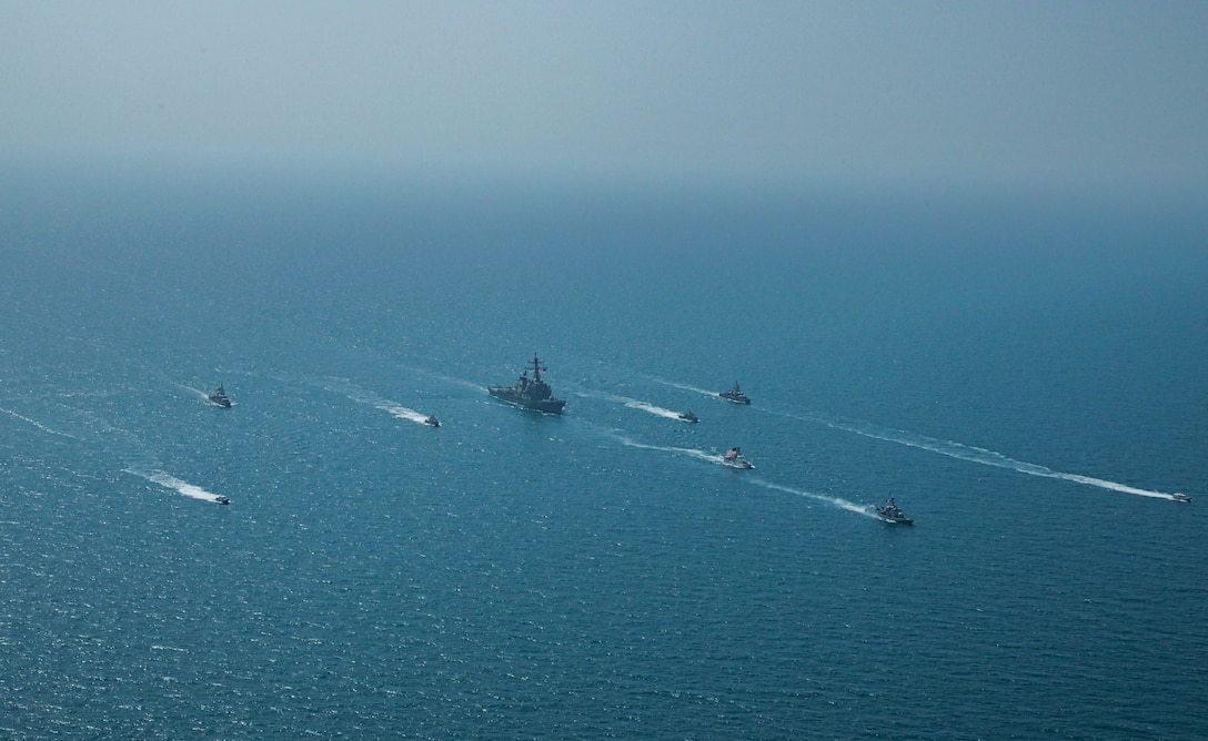 Royal Bahrain Naval Force fast attack craft RBNS Abdul Rahman Al-fadel (P 22), Bahrain Coast Guard response boats Hawar 5 and Hawar 4, U.S. Navy guided-missile destroyer USS Mahan (DDG 72), patrol coastal ships USS Squall (PC 7) and USS Hurricane (PC 3), U.S. Coast Guard patrol boat USCGC Adak (WBP 1333) and two Mark VI patrol boats operate in formation during exercise Neon Defender in the Arabian Gulf, April 7. Neon Defender 21 is a bilateral maritime exercise between the U.S. and Bahrain, designed to enhance interoperability and readiness, fortify military-to-military relationships and advance operational capabilities, allowing participating naval forces to effectively develop the necessary skills to address threats to regional security, freedom of navigation and the free flow of commerce. (Army Photo by Spc. Evens Milcette Jr.)