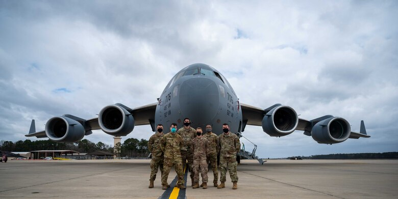 Team Dover's Multi-Capable Airmen team poses for a photo in front of a Dover AFB C-17 Globemaster III during exercise Razor Talon at Seymour Johnson AFB, North Carolina, March 22, 2021. The base's MCA program developed and equipped seven Airmen to perform tasks outside of their Air Force Specialty Codes. Exercises such as RT help integrate MCA into joint and combined expeditionary operations around the globe.  (U.S. Air Force photo by Airman 1st Class Faith Schaefer)