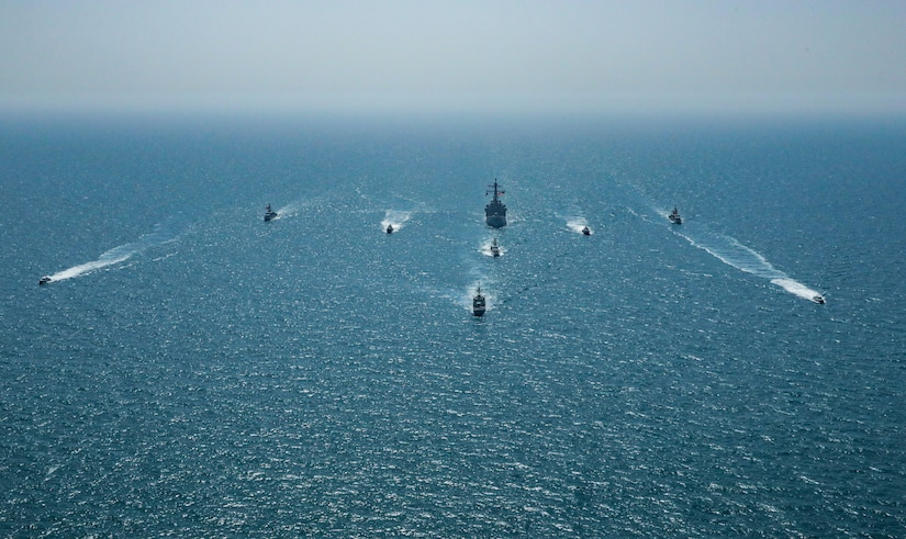 A group of vessels sail in formation through blue waters.