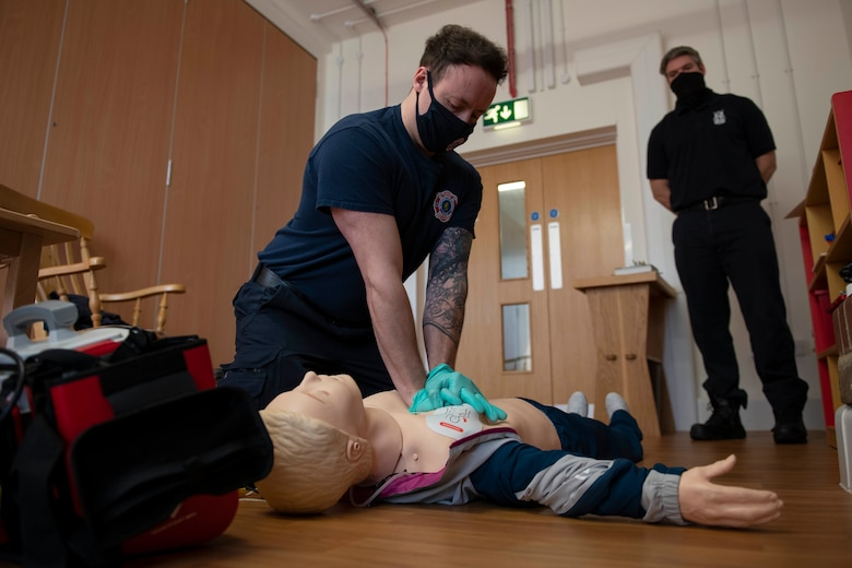 Tom Reynolds, left, 423rd Civil Engineer Squadron firefighter, conducts CPR on a simulated patient during an EMT practical application exam at Royal Air Force Croughton, England, March 31, 2021. U.K. firefighters across the 501st Combat Support Wing were tested in a practical application of their knowledge and skills, after attending over 280 hours of the U.S. National Registry of Emergency Medical Technicians course. The primary mission of the course was to prepare the fire department to respond to medical emergencies, as EMTs assume the responsibility of operating the ambulances and transporting patients to medical facilities. (U.S. Air Force photo by Senior Airman Jennifer Zima)