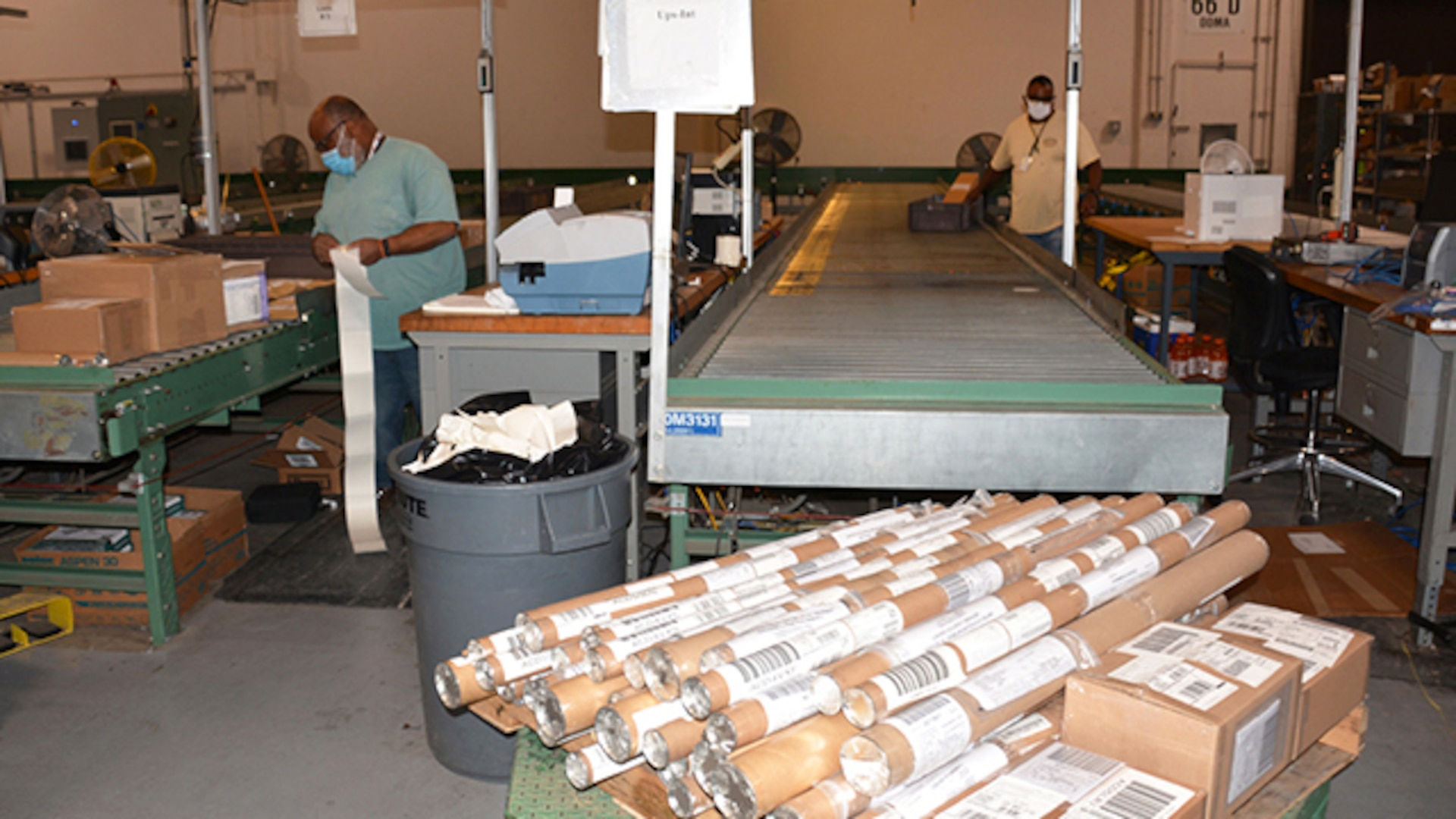 Edward Seaborne, Jr. and Carlton Drummond, both materials handlers from Defense Logistics Agency Distribution, prepare packages to mail mapping products to customers