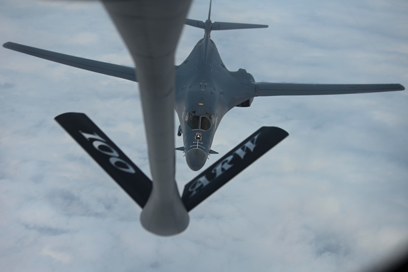 An aircraft is refueled by another aircraft in mid-air.