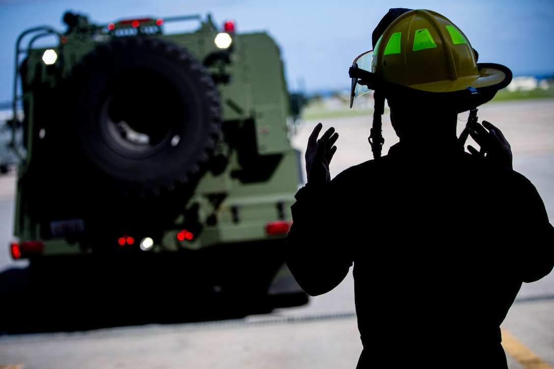 U.S. Marine Corps Pfc. Elijah Stewart, an expeditionary firefighting and rescue (EFR) specialist with Headquarters and Headquarters Squadron (H&HS), Marine Corps Installations Pacific, guides an Oshkosh P-19R Aircraft Rescue and Firefighting Vehicle after a turret drill on Marine Corps Air Station Futenma, Okinawa, Japan, April 7, 2021.  EFR specialist Marines with H&HS provide aircraft rescue and firefighting services in support of airfield operations and respond to any fire-related emergencies and situations with a maximum response time of five minutes. Stewart is a native of Independence, Missouri. (U.S. Marine Corps photo by Lance Cpl. Alex Fairchild)