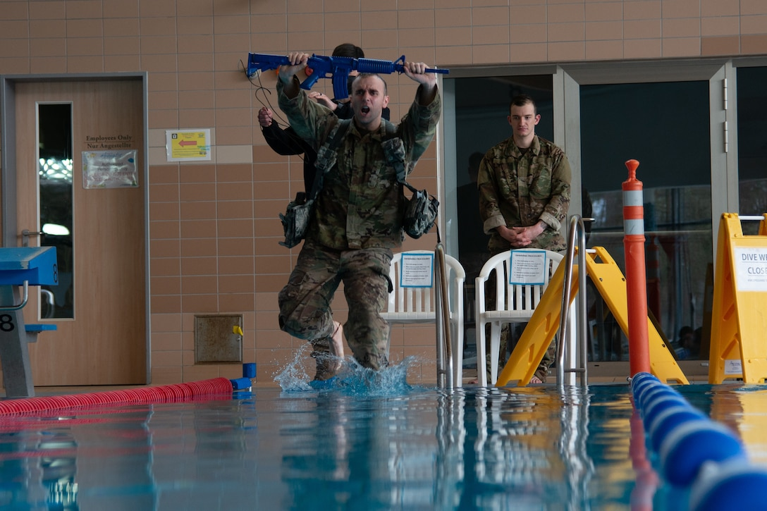 Man in uniform holding training weapon jumps in pool