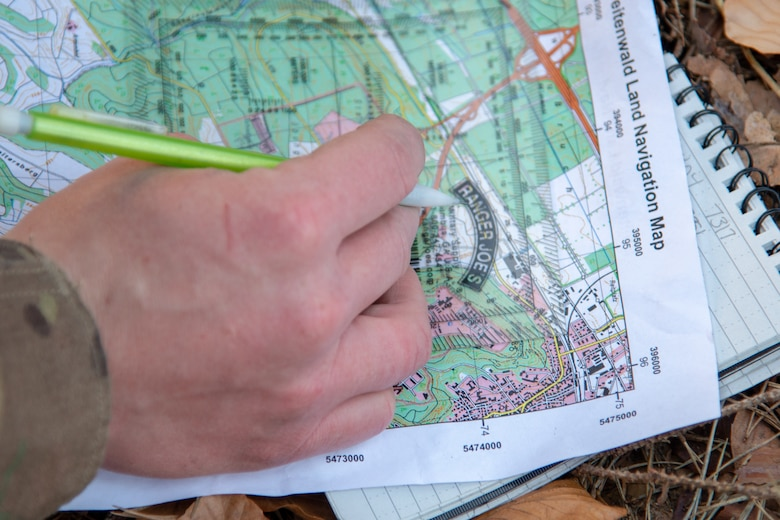 Close up of hand holding map and pencil
