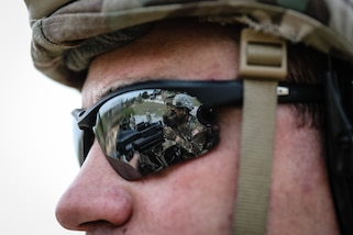 """A U.S. Army Reserve Soldier watches Spc. Daniel P. Bush, Jr., a civil affairs specialist with the 418th Civil Affairs Battalion, fire a Mk 19 automatic grenade launcher during day one of the 2021 U.S. Army Civil Affairs and Psychological Operations Command (Airborne) Best Warrior Competition at Fort Jackson, S.C., April 8, 2021. The USACAPOC(A) BWC is an annual event that brings in competitors from across USACAPOC(A) to earn the title of """"Best Warrior."""" BWC tests the Soldiers' individual ability to adapt and overcome challenging scenarios and battle-focused events, testing their technical and tactical skills under stress and extreme fatigue."""