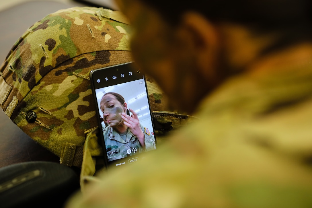 """U.S. Army Reserve Spc. Arianna Hammel, an intelligence analyst with the 15th Psychological Operations Battalion, applies camouflage paint to prepare for a range qualification during day one of the 2021 U.S. Army Civil Affairs and Psychological Operations Command (Airborne) Best Warrior Competition at Fort Jackson, S.C., April 8, 2021. The USACAPOC(A) BWC is an annual event that brings in competitors from across USACAPOC(A) to earn the title of """"Best Warrior."""" BWC tests the Soldiers' individual ability to adapt and overcome challenging scenarios and battle-focused events, testing their technical and tactical skills under stress and extreme fatigue."""