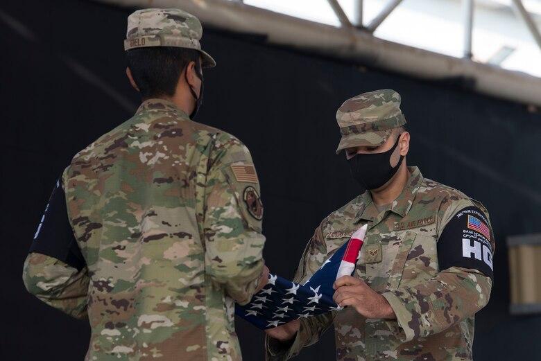 Senior Airman May Zamora Castillo folds a U.S. flag during a ceremony.