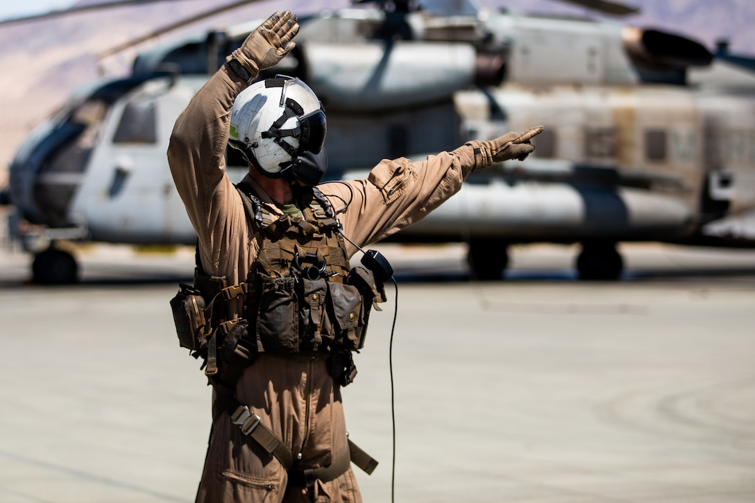 U.S. Marine Corps Staff Sgt. Joshua D. Perkins, a crew chief with Marine Heavy Helicopter Squadron (HMH) 366, guides pilots using hand and arm signals prior to takeoff at Marine Air-Ground Combat Center, California, March 31, 2021. HMH-366 and other squadrons assigned to Marine Air Group (MAG) 29 are training to integrate with and support various Marine ground units as part of Service Level Training Exercise (SLTE) 3-21. SLTE is a series of exercises designed to prepare Marines for operations around the globe by increasing their ability to operate and conduct offensive and defensive combat operations. MAG-29 is a subordinate unit of 2nd Marine Aircraft Wing, the aviation combat element of II Marine Expeditionary Force. (U.S. Marine Corps photo by Lance Cpl. Elias E. Pimentel III)