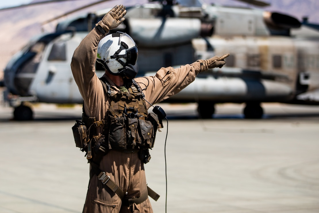 U.S. Marine Corps Staff Sgt. Joshua D. Perkins, a crew chief with Marine Heavy Helicopter Squadron (HMH) 366, guides pilots using hand and arm signals prior to takeoff at Marine Air-Ground Combat Center, California, March 31, 2021.