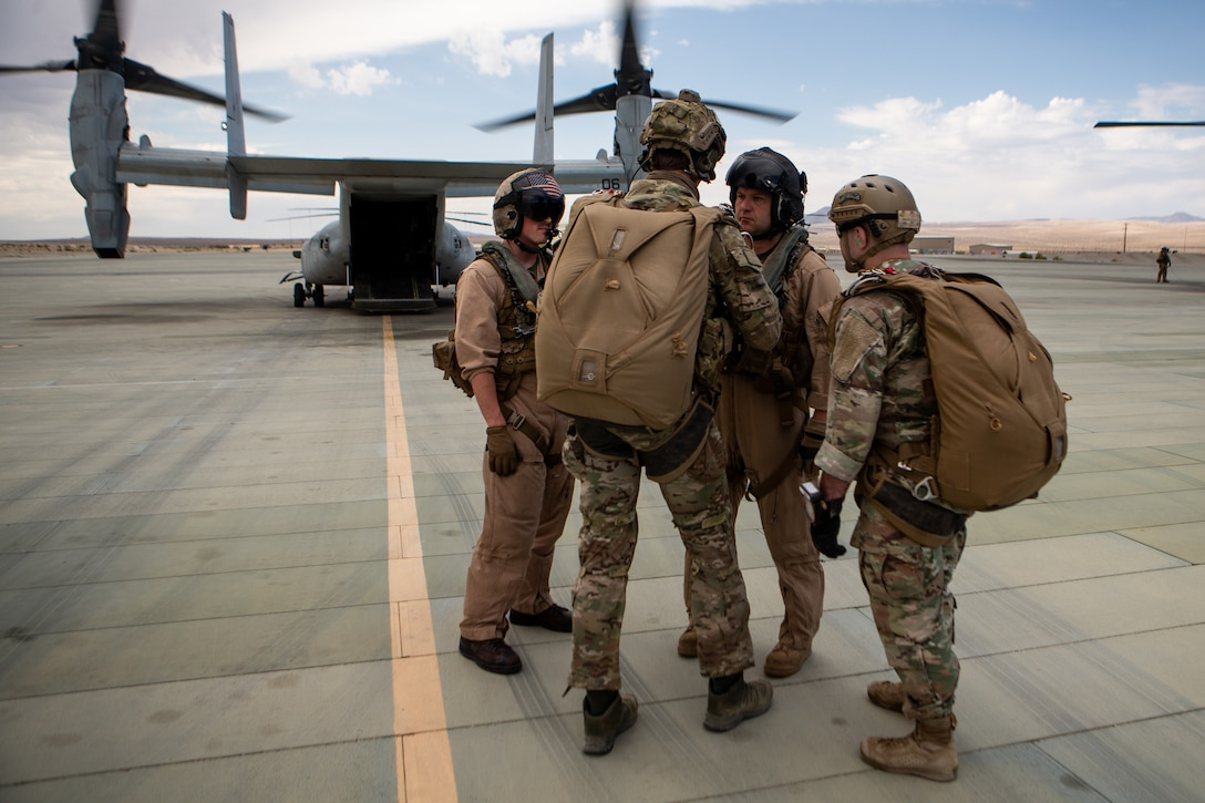 U.S. Army Soldiers assigned to 10th Special Forces Group (Airborne) discuss flight plans with Marines from Marine Medium Tiltrotor Squadron (VMM) 365 at Marine Air-Ground Combat Center, California, April 1, 2021. Marines with Marine Medium Tiltrotor Squadron 365 and Soldiers with 10th SFG (A) prepare for future conflicts in the integrated and joint environment provided by Service Level Training Exercise (SLTE) 3-21. SLTE is a series of exercises designed to train Marines for operations around the globe by increasing their ability to operate and conduct offensive and defensive combat operations. VMM-365 is a subordinate unit of 2nd Marine Aircraft Wing, the aviation combat element of II Marine Expeditionary Force. (U.S. Marine Corps photo by Lance Cpl. Elias E. Pimentel III) (This photo has been altered for security purposes by blurring out the servicemember's face and other personal identifying elements.)