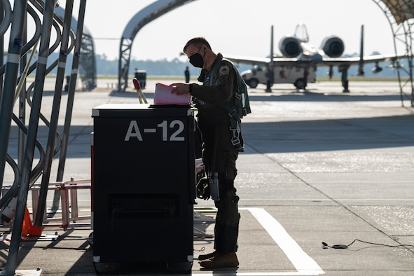 A photo of an Airman looking at a booklet.