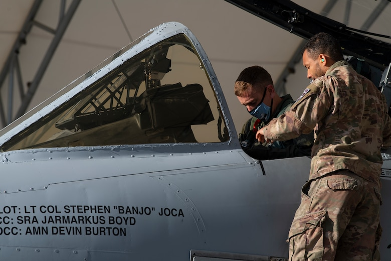 A photo of an Airman standing on a ladder outside of an A-10C Thunderbolt II, handing an object to another Airman.