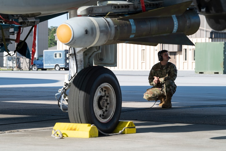 A photo of an Airman crouching underneath and A-10C Thunderbolt II.