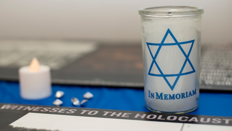Memorial candles and gems are displayed at a Holocaust Memorial at MacDill Air Force Base, Fla., April 8, 2021.