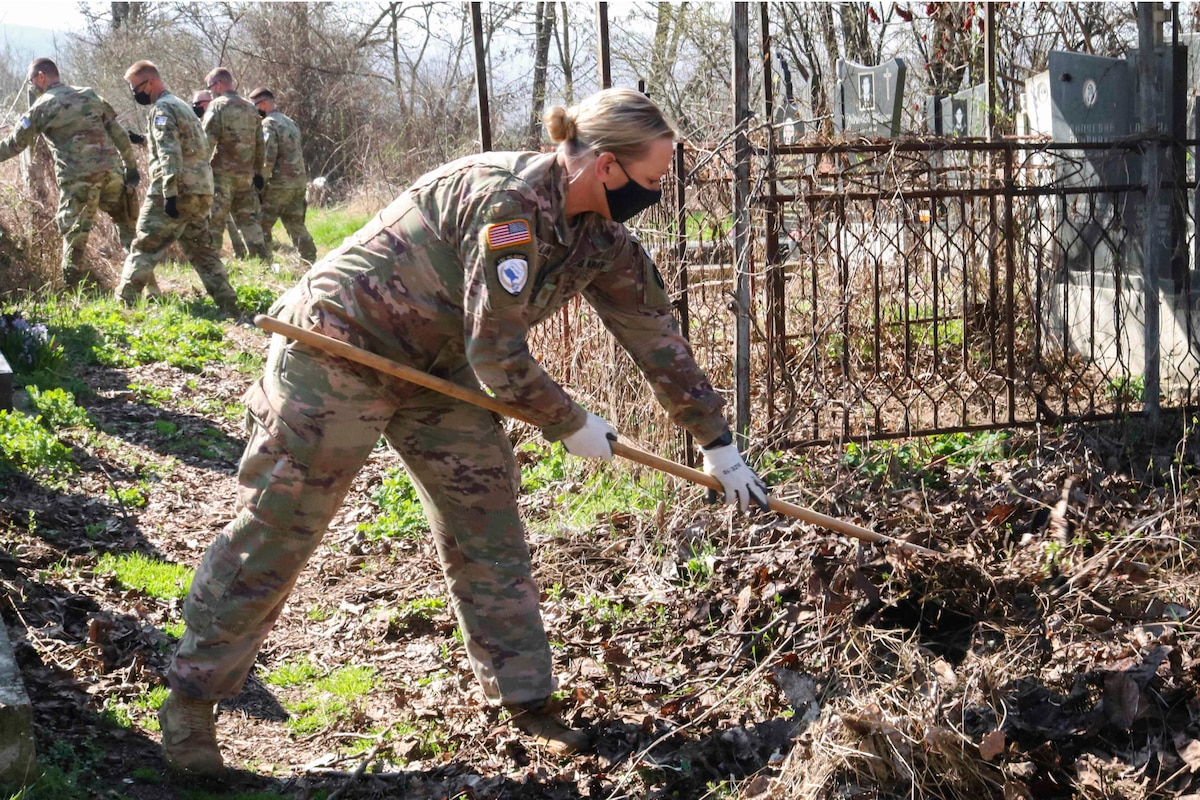 A soldier rakes weeds at a cemetery.
