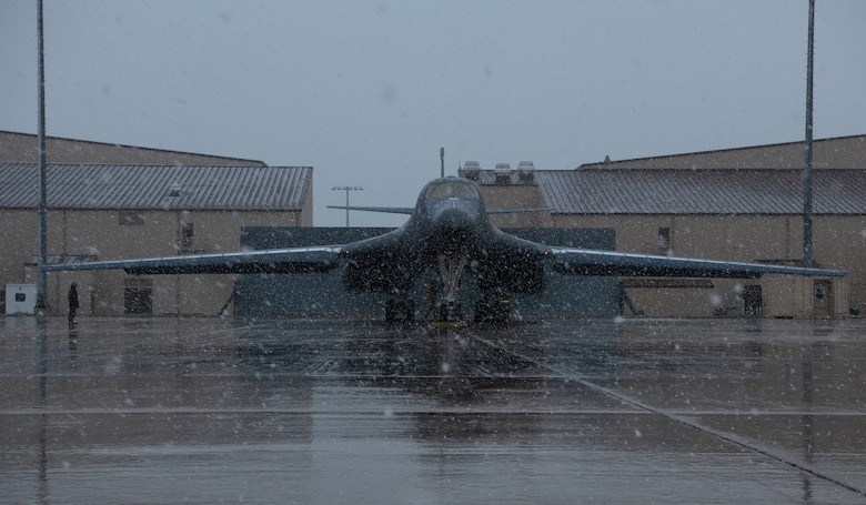 Light snow falls on a B-1B Lancer being prepared for a Bomber Task Force mission at Ellsworth Air Force Base, S.D., April 6, 2021.