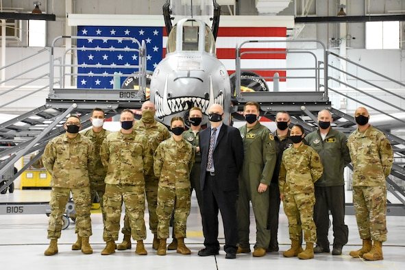 Acting Secretary of the Air Force John Roth departs the 5-Bay hangar with Colonel Jeffrey Schreiner in front of a large American flag.