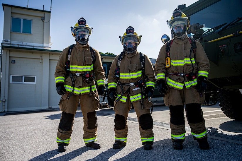 Three Marines wearing fire protective gear pose for a photo.