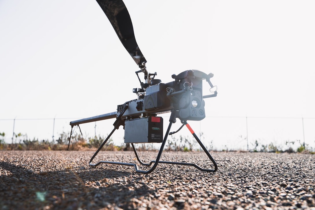 A small drone sits on the ground.